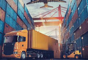 Foto ilustrativa de um caminhão estacionado ao lado de contêineres
